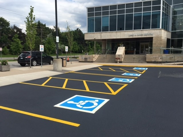 Sealcoated parking lot with symmetric parking yellow lines and ADA services