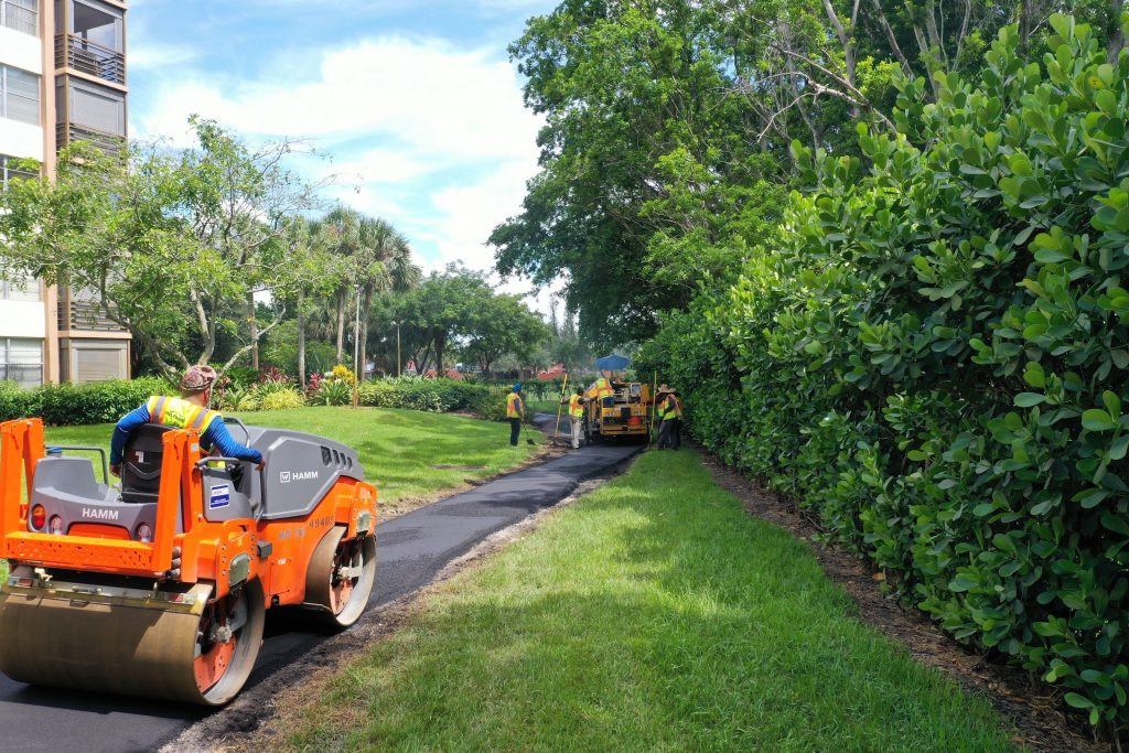 Asphalt road with a paver near grass and some trees