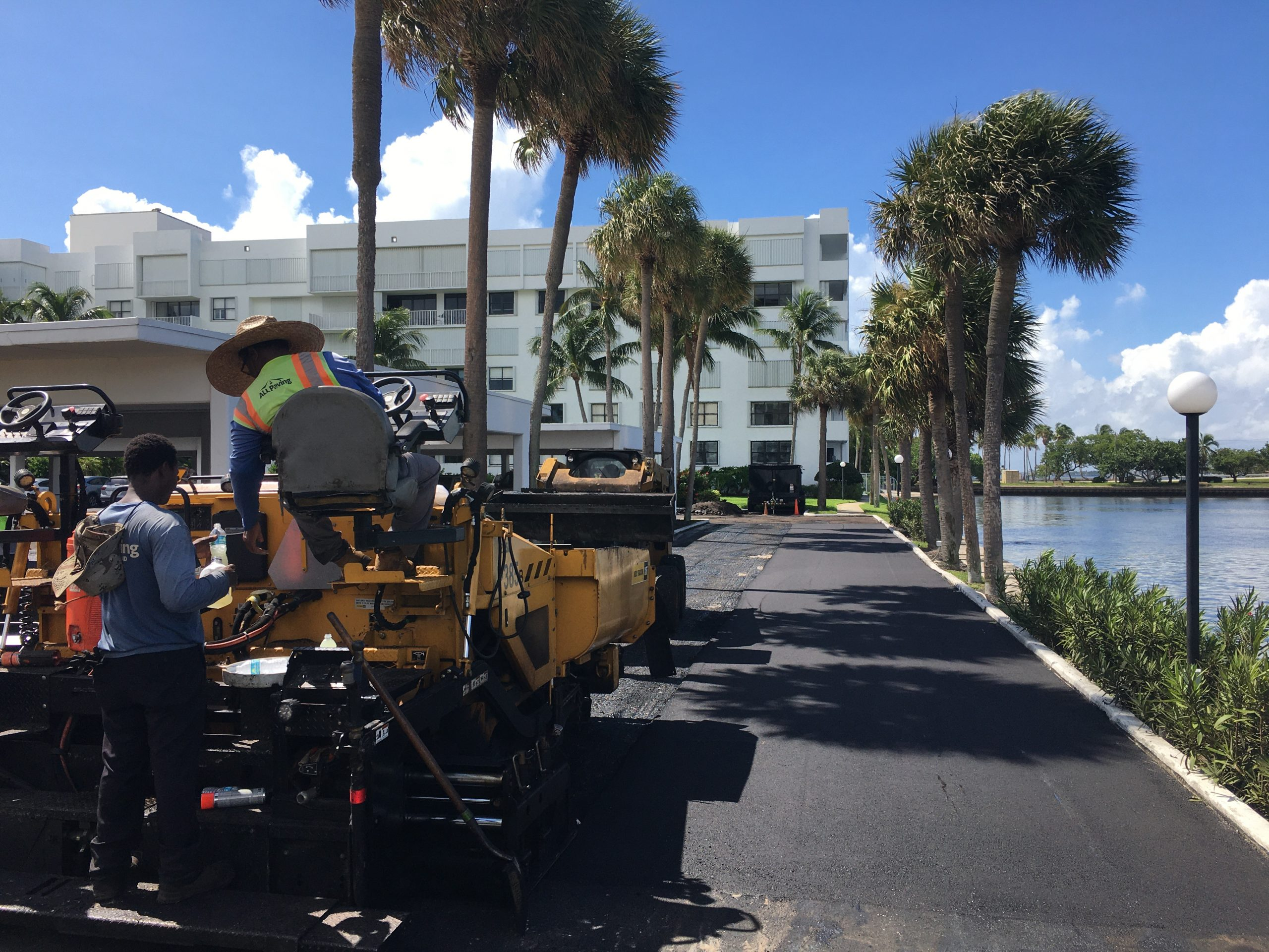 Asphalt paving equipment on public road beside water on a sunny day