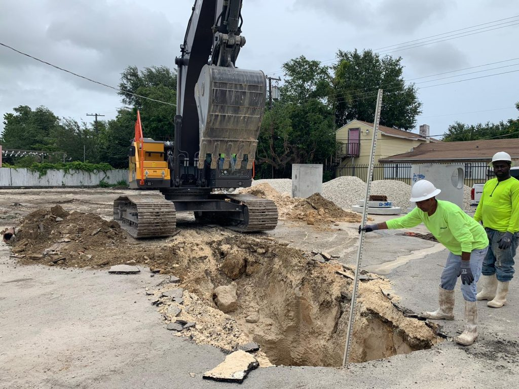 Excavator working on a drainage process with All Paving Inc.
