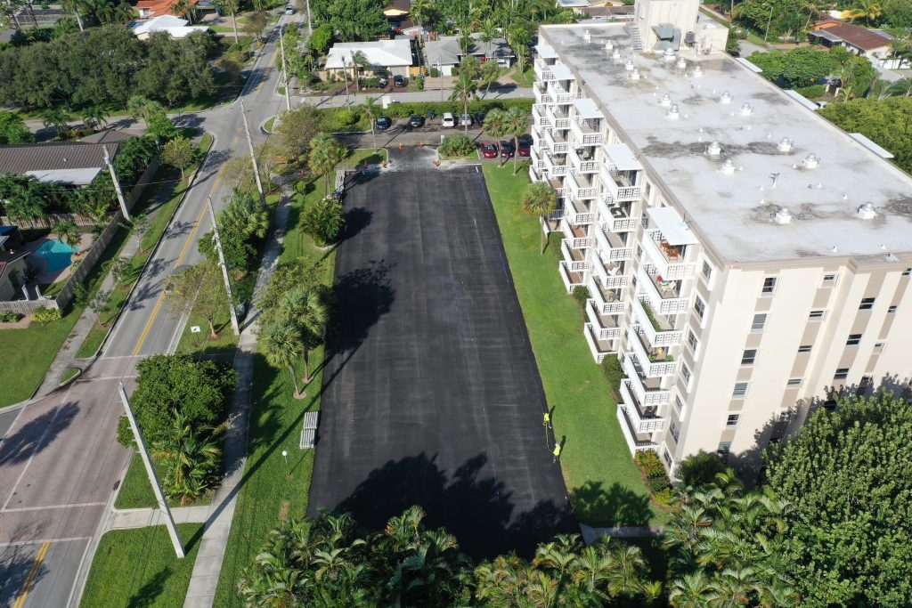 Parking lot surface after asphalt milling and Paving, undergoing striping process.