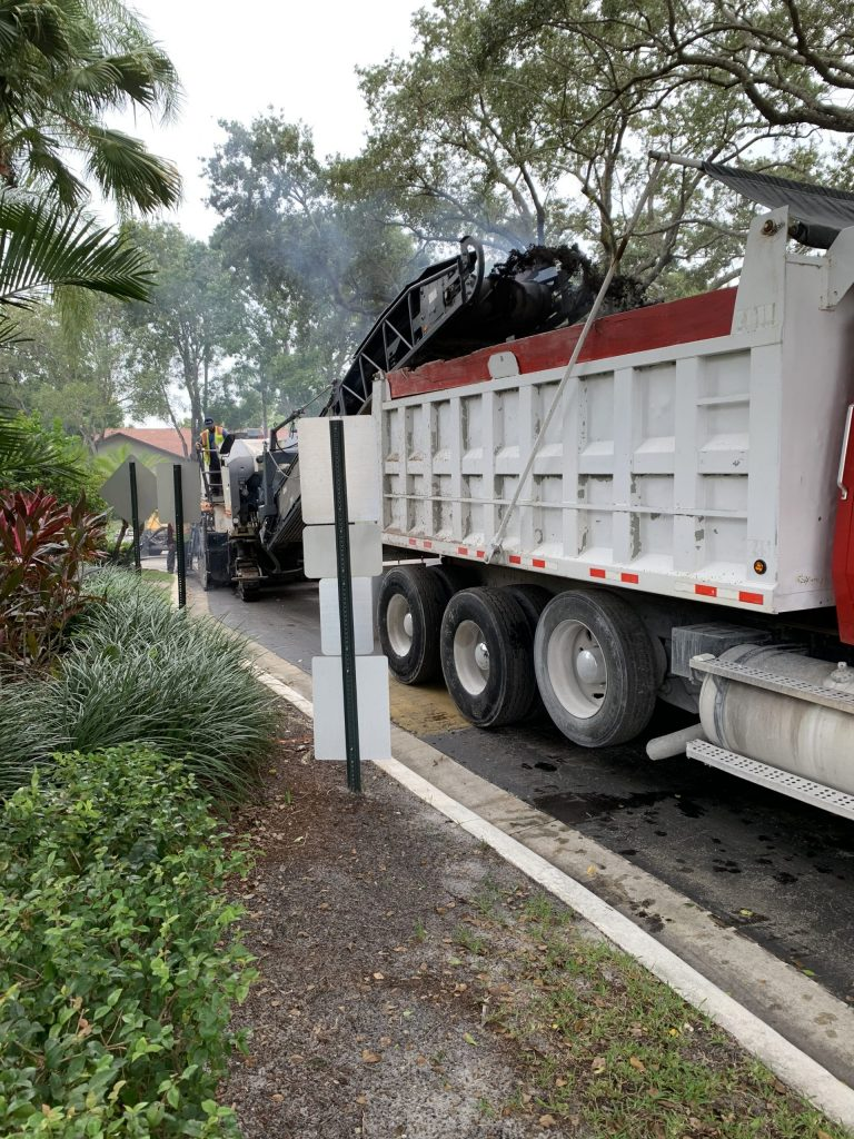 Milling machine with truck in front while doing asphalt milling