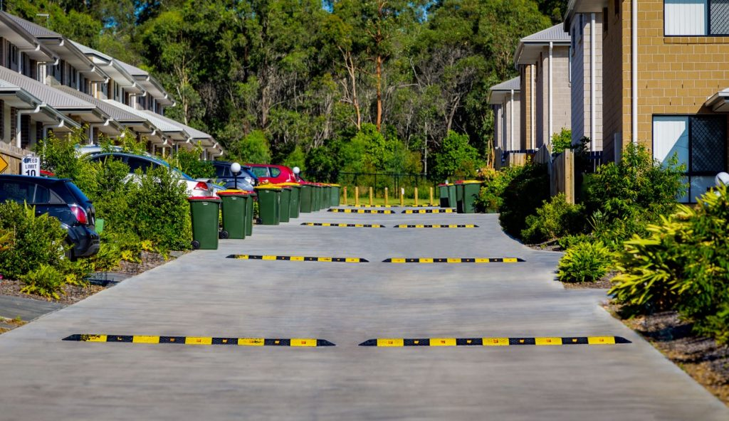 Driveway with black and yellow speed bumps